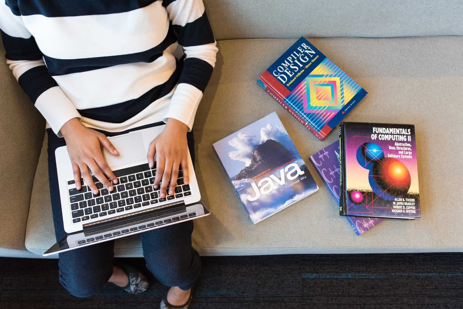 A person types on a keyboard next to coding textbooks