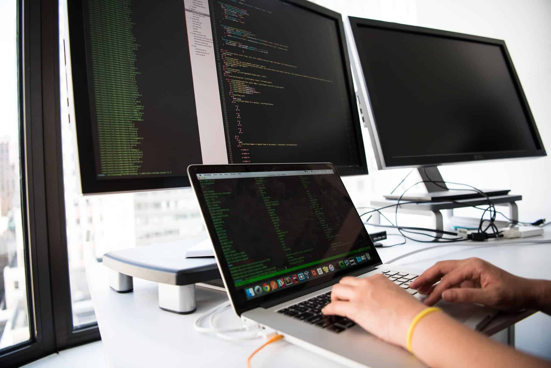 A person typing lines of code facing multiple monitors