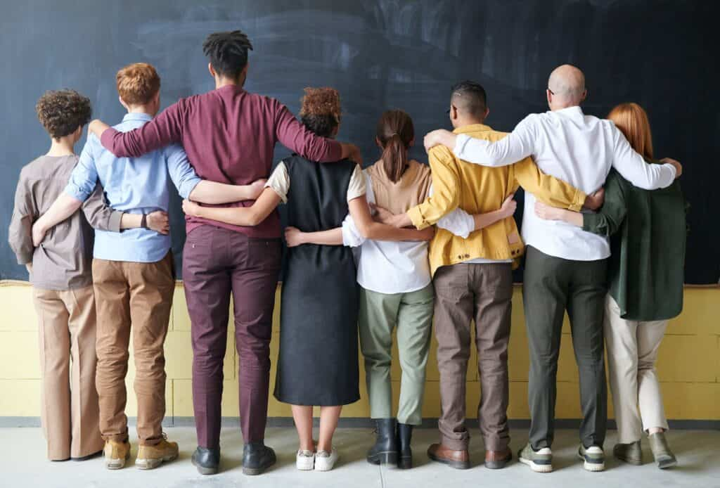a group of people lining up and holding each other's backs