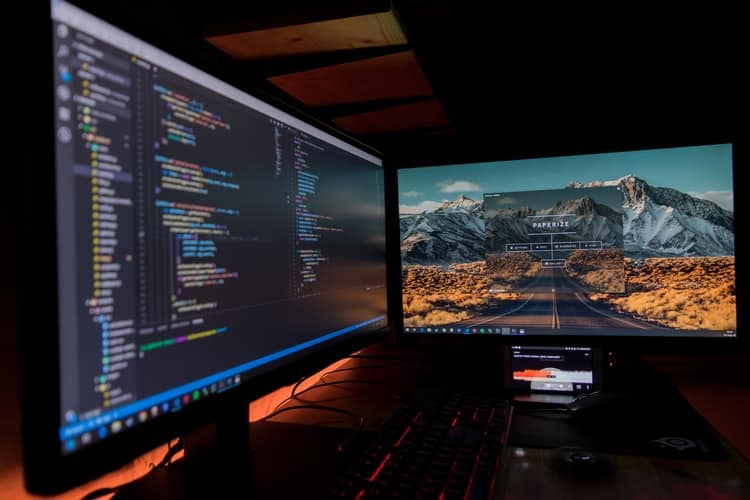 Two black computer monitors displaying code
