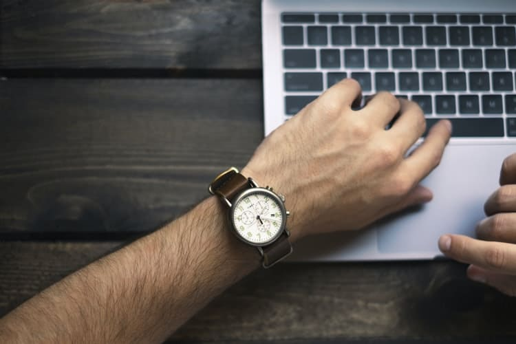 a person wearing wristwatch and using laptop