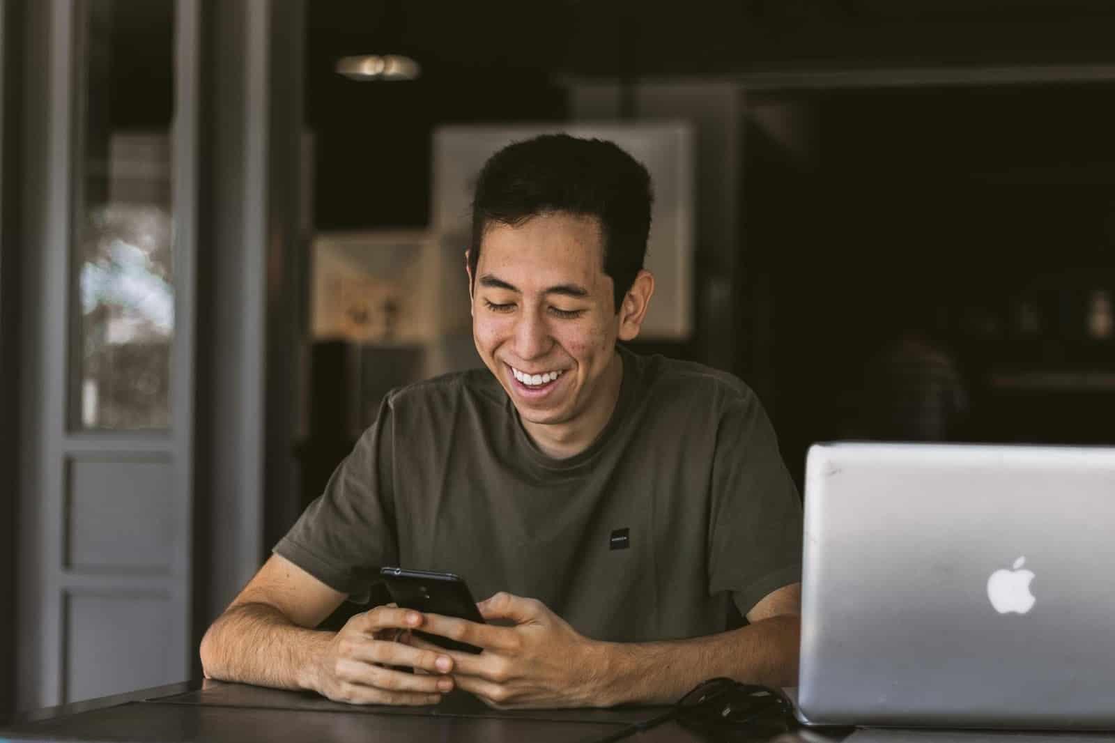 man smiling and checking phone
