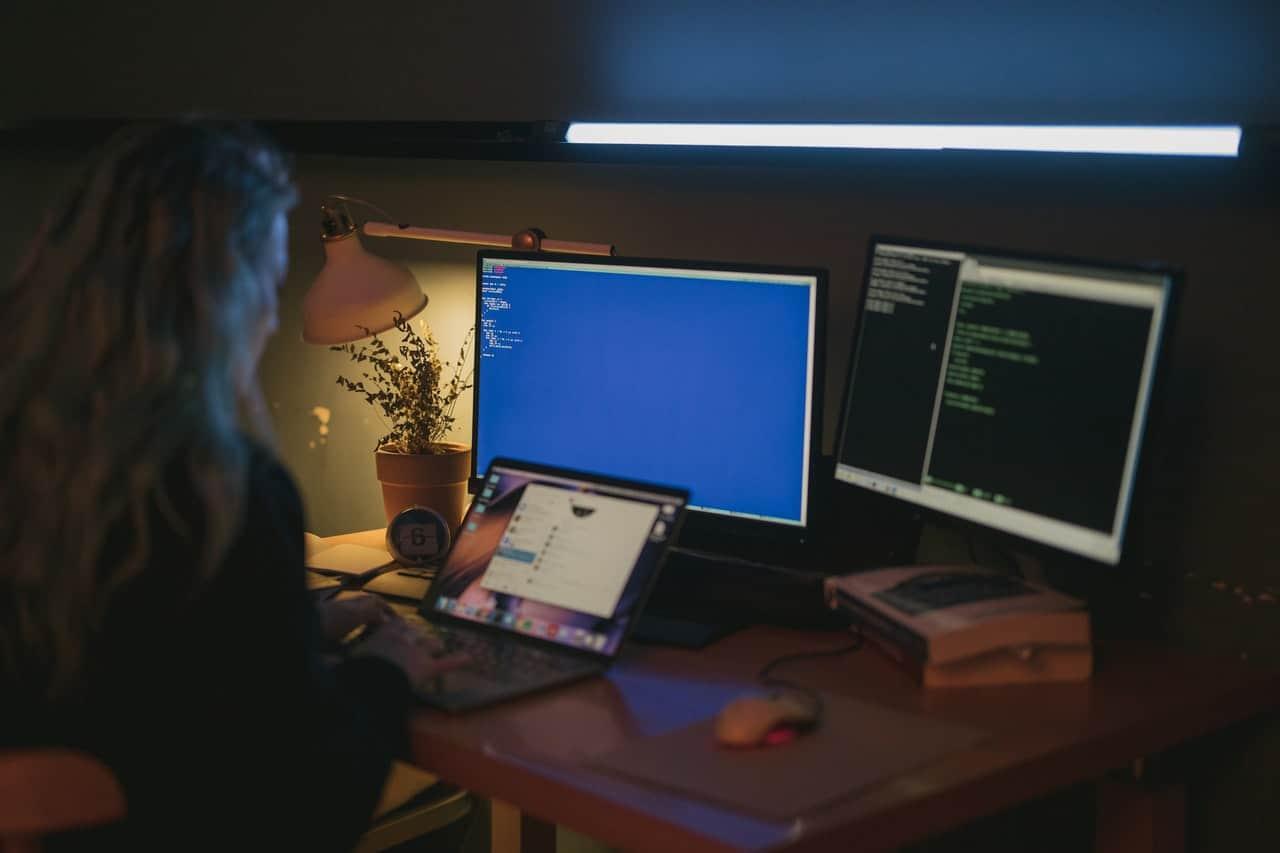 Woman coding on computer screens