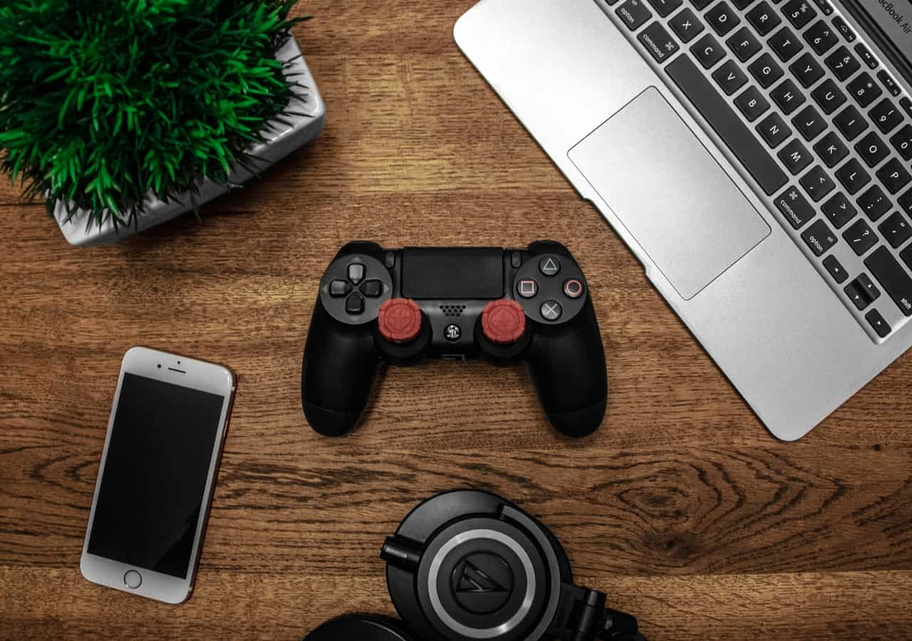 a video game controller, laptop and mobile phone on desk