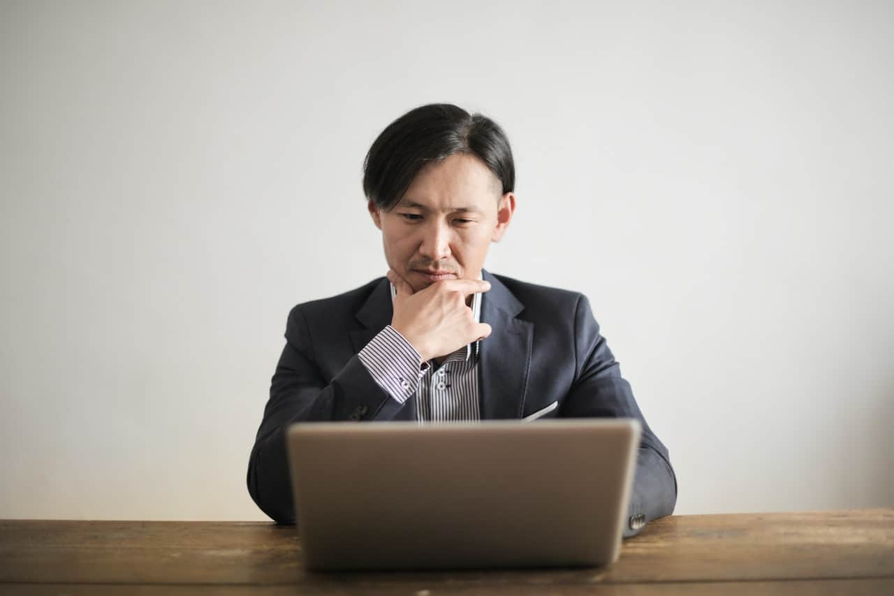 Man looking contemplatively at a laptop computer screen