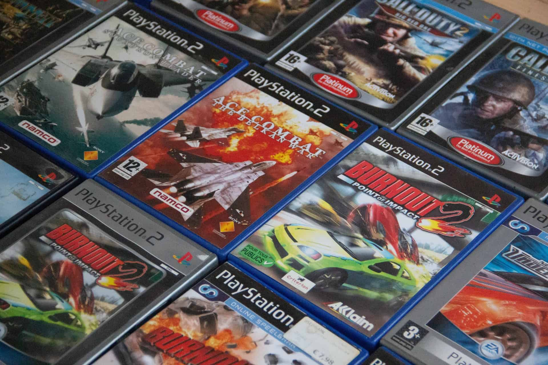 A variety of PlayStation games are arranged on a table.