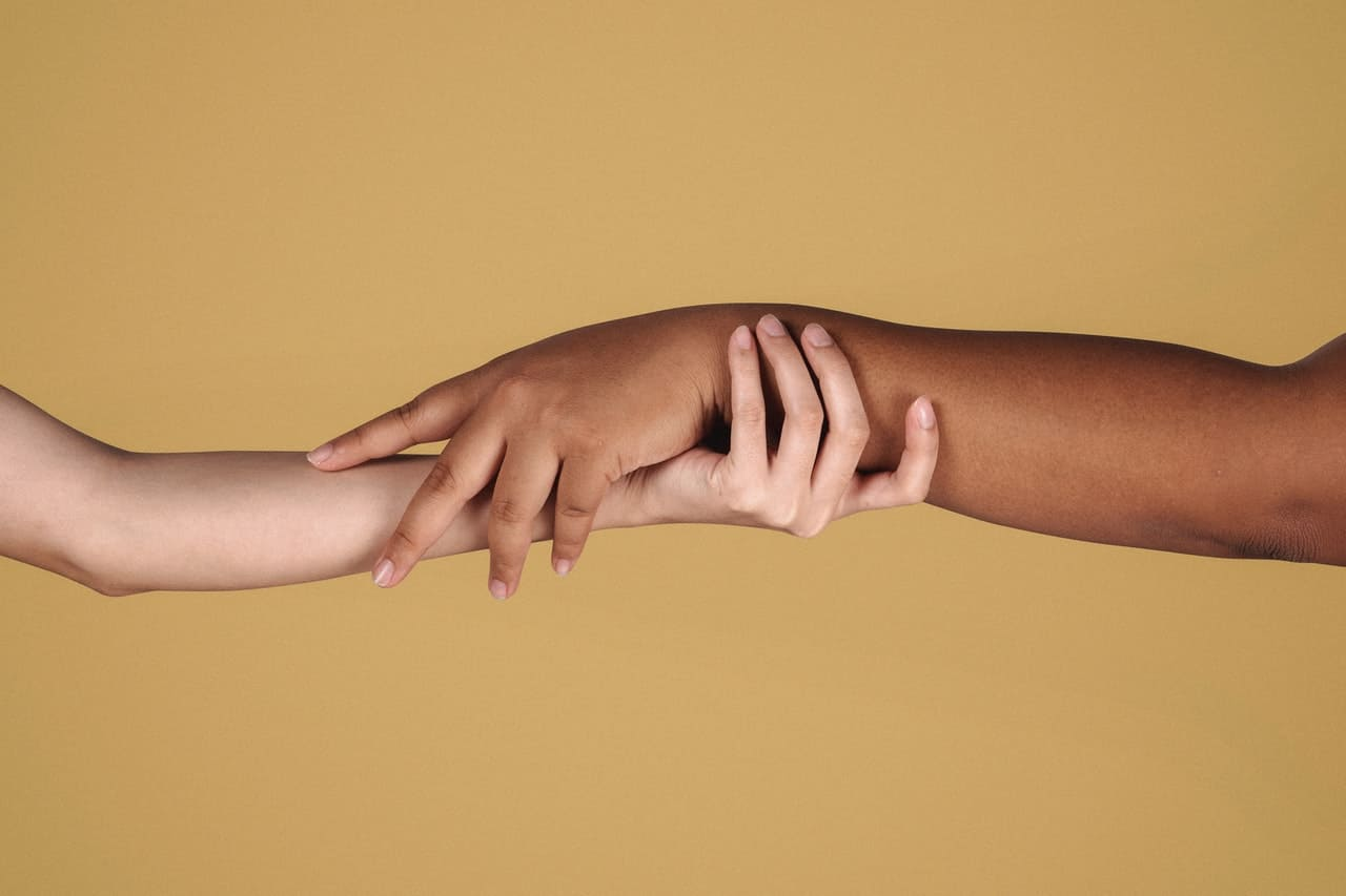 Diverse women showing respect to each other while holding hands.