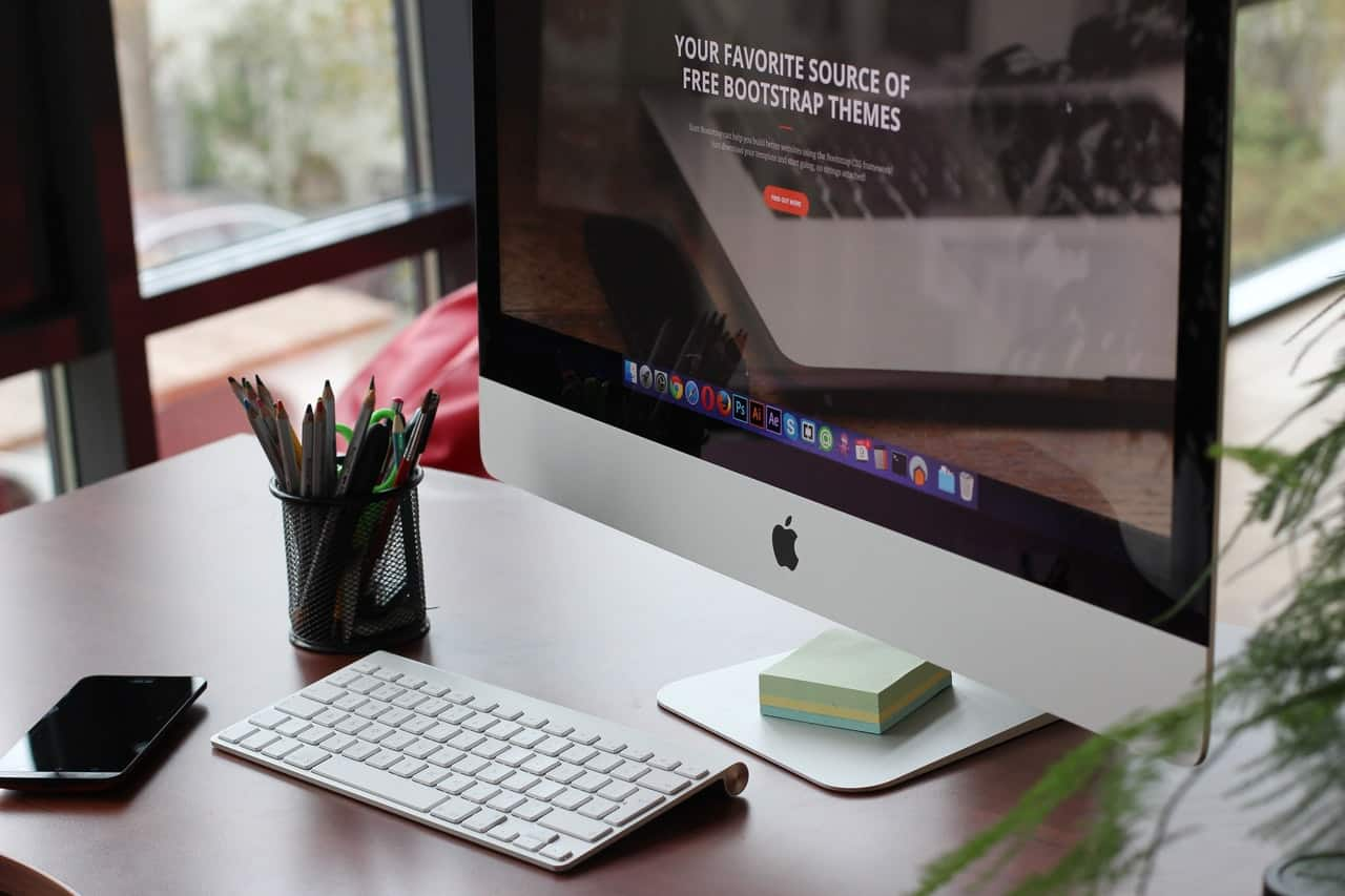 """an iMac on desk displaying the text """"your favorite source of free Bootstrap themes"""""""