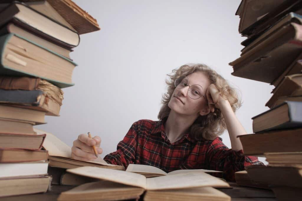woman studying infosec in between piles of books
