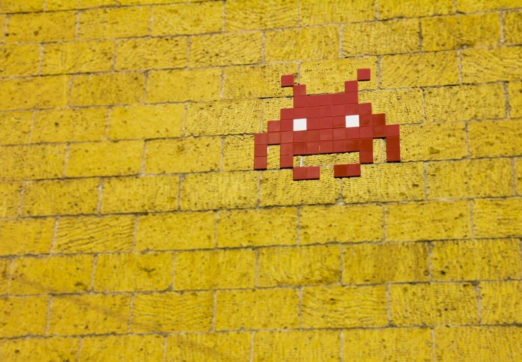 a red, pixelated game character on yellow wall