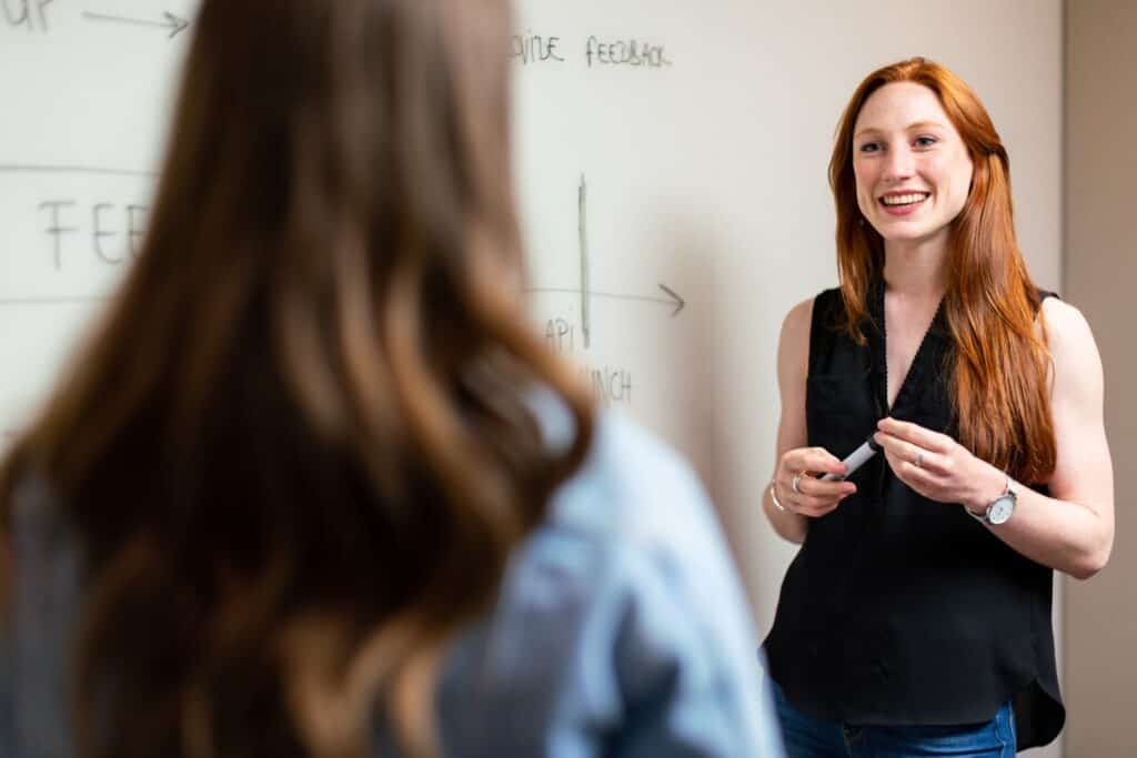 a woman discussing in front of whiteboard