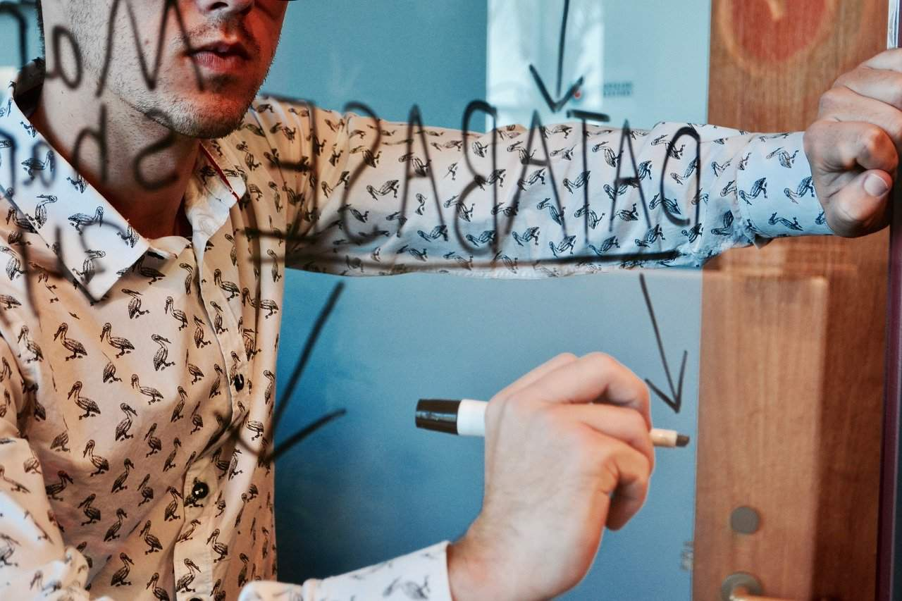 a man drawing database framework on a board
