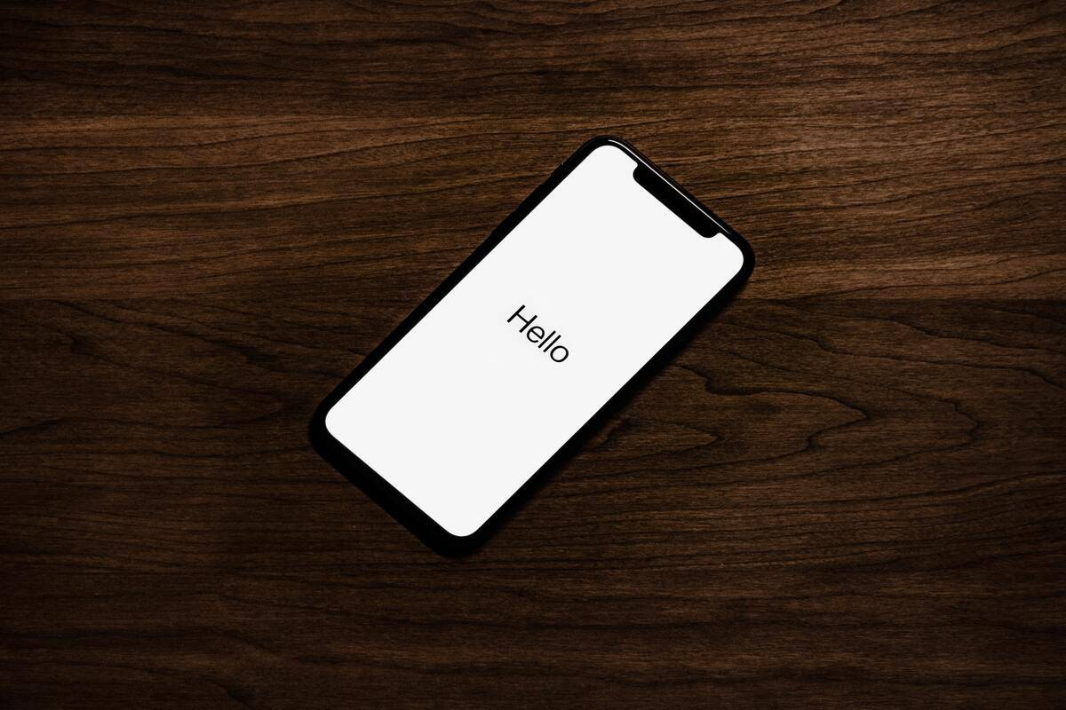 """An iPhone displaying a """"Hello"""" message sits on a wooden table."""
