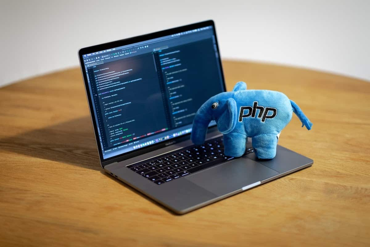 : a blue elephant plush with PHP lettering on the side sitting atop a Macbook Pro with PHP code on the screen
