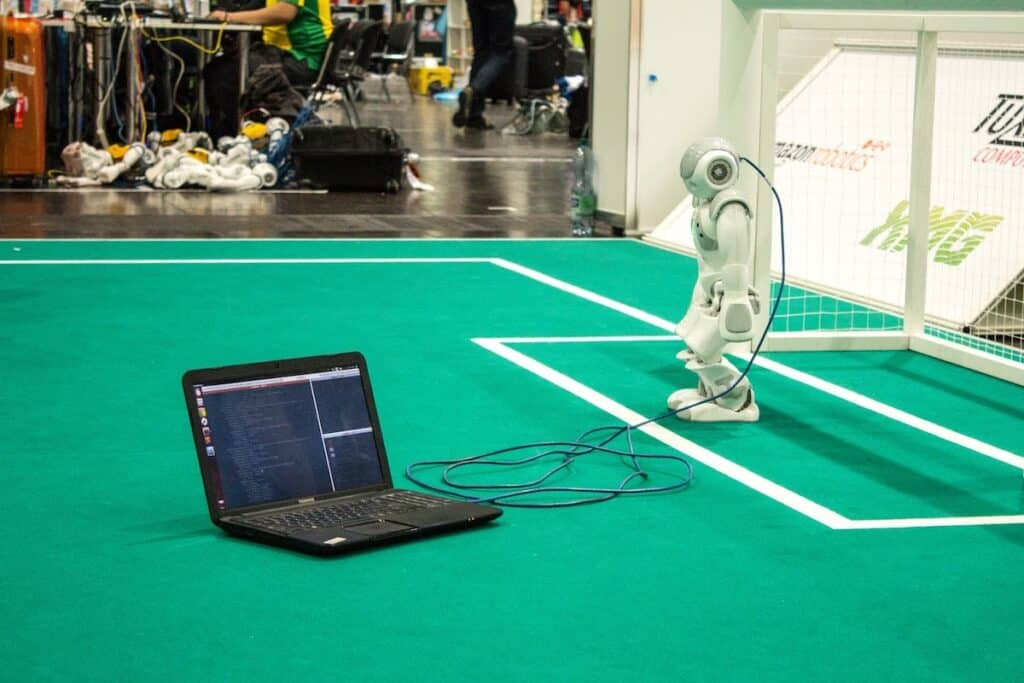 A computer connects to a humanoid robot standing on a soccer field.