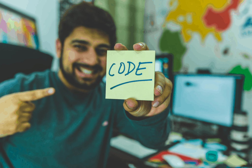 Man holding up post-it note with 'CODE' written on it