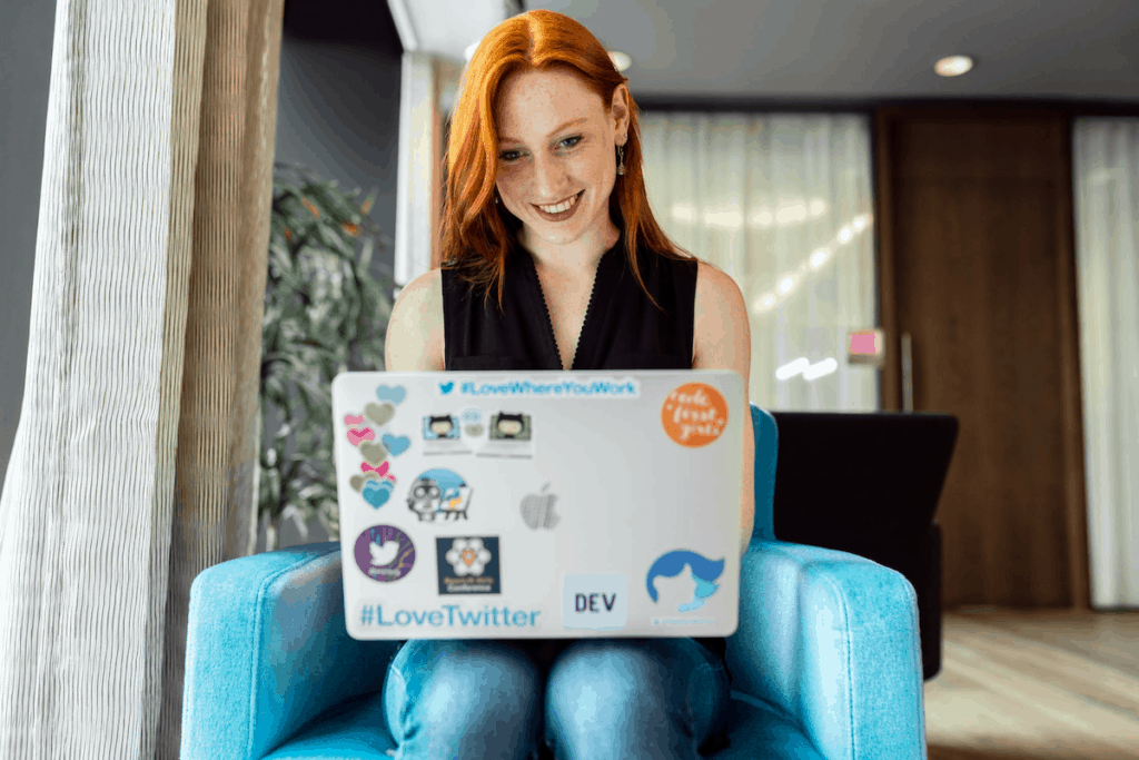 Red-haired woman smiling and typing on her laptop computer