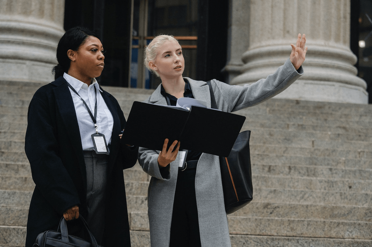 two women outside on steps with a sheaf of documents discussing management