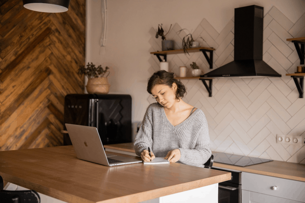 a woman at her kitchen counter writing on a notebook in front of her MacBook.
