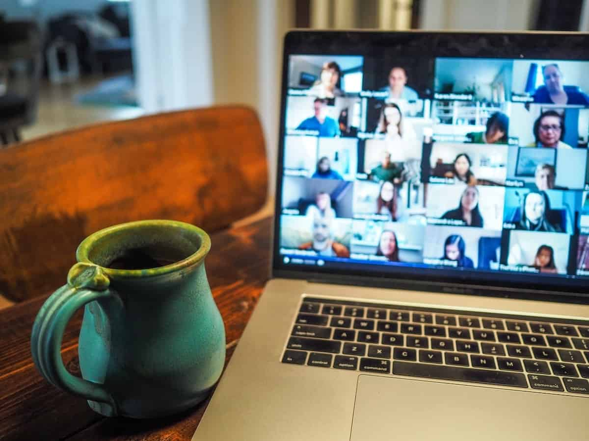 a coffee mug next to a Macbook Pro displaying a group call page