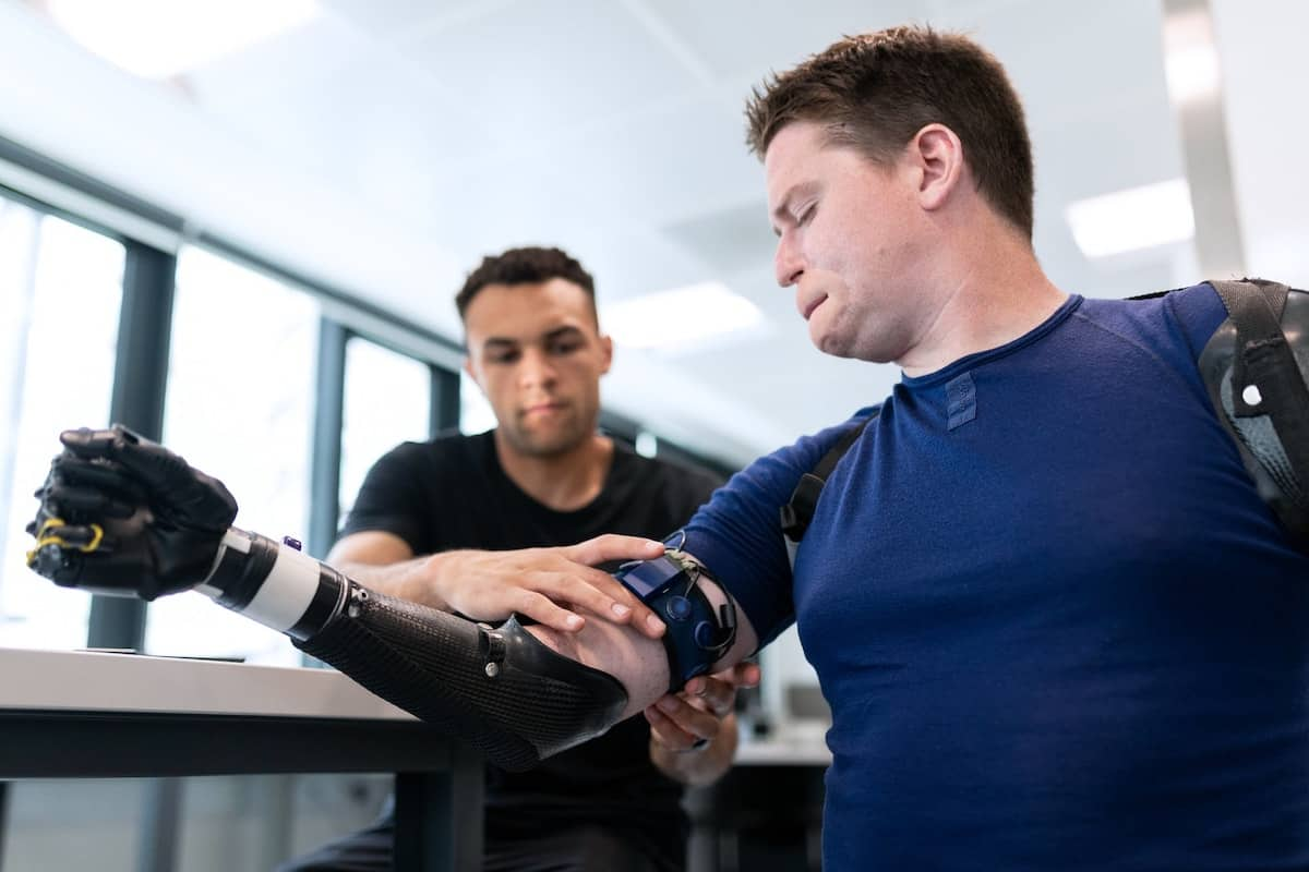a man in a blue t-shirt being fitted for a prosthetic arm