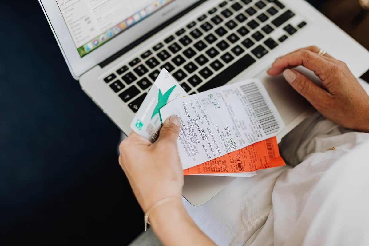 a person holding credit card and receipt while using laptop