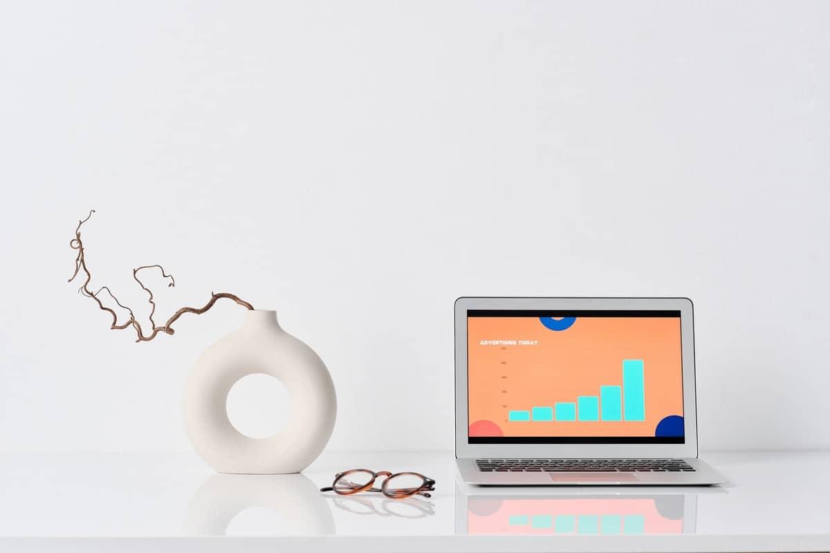 """a white jar with laptop displaying """"Advertising"""""""
