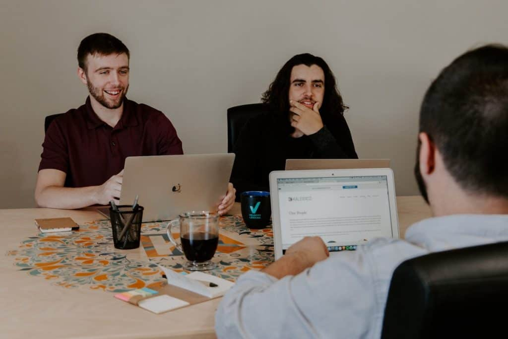 Three men with laptops sit around a table in a learning environment How Long Does It Take to Learn a Programming Language