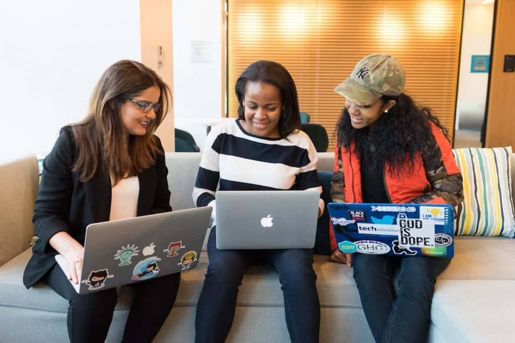 Three people of color attending a virtual event on their laptops Coding Bootcamp for Women