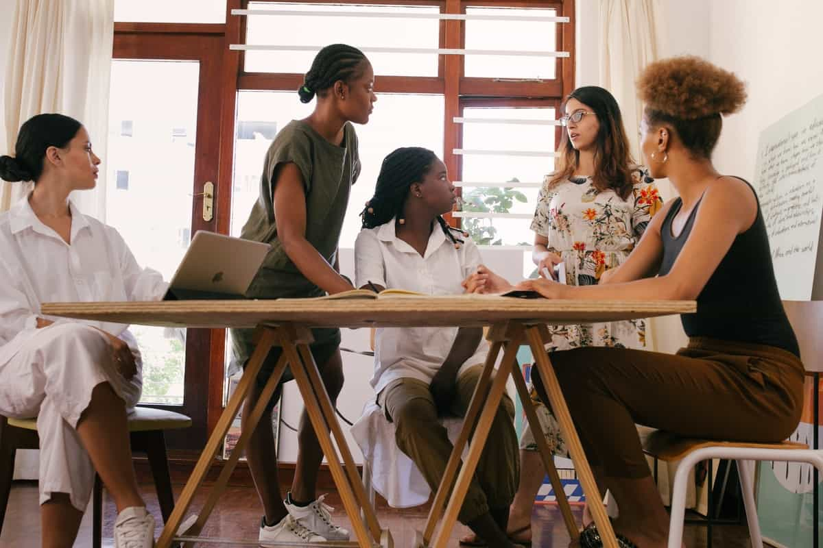 five women around a table, three sitting and two standing Coding Bootcamp for Women