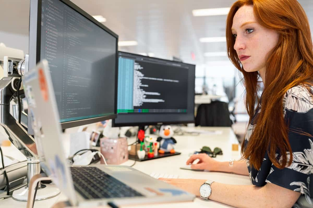Woman coding on three computers simultaneously Computer Science vs Computer Engineering