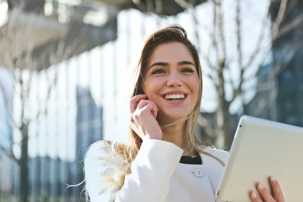 A woman holding an iPad in and smiling. How to Make a Career Change