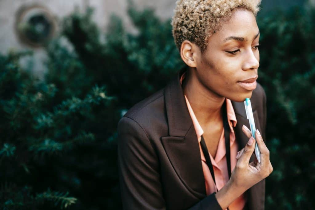 Woman in business suit with a pen resting on her chin Data Analyst Salary