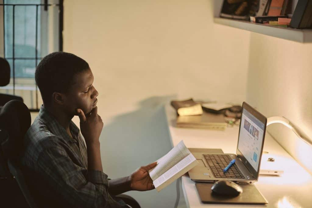 A coder reading a book with his laptop open in front of him Ruby vs Python: Which One Should Be Your First Programming Language?