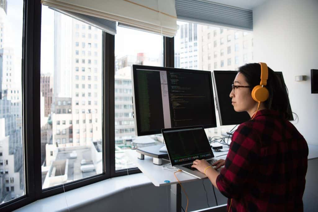 A woman wearing a headset looking at three computer displays. Web vs Mobile Development: Which Should You Learn First?