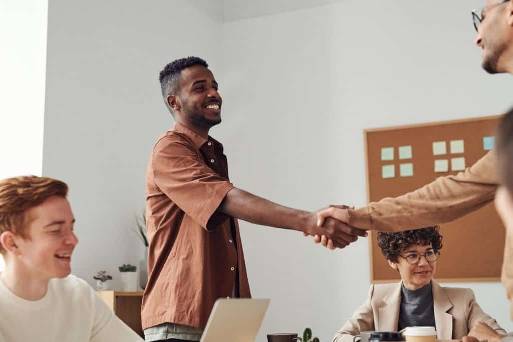 Man in brown shirt shaking hands with another man Getting a Job After a Coding Bootcamp