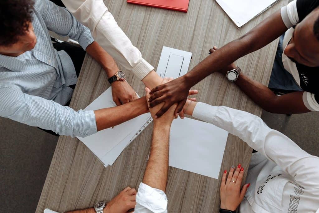 Colleagues shaking hands as a team. Tech Jobs That Pay $100K