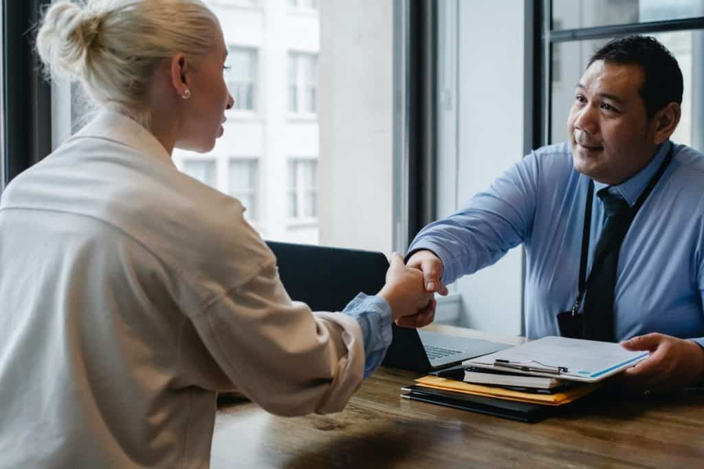 A woman shaking hands with a man. How to Develop Your Programming Portfolio