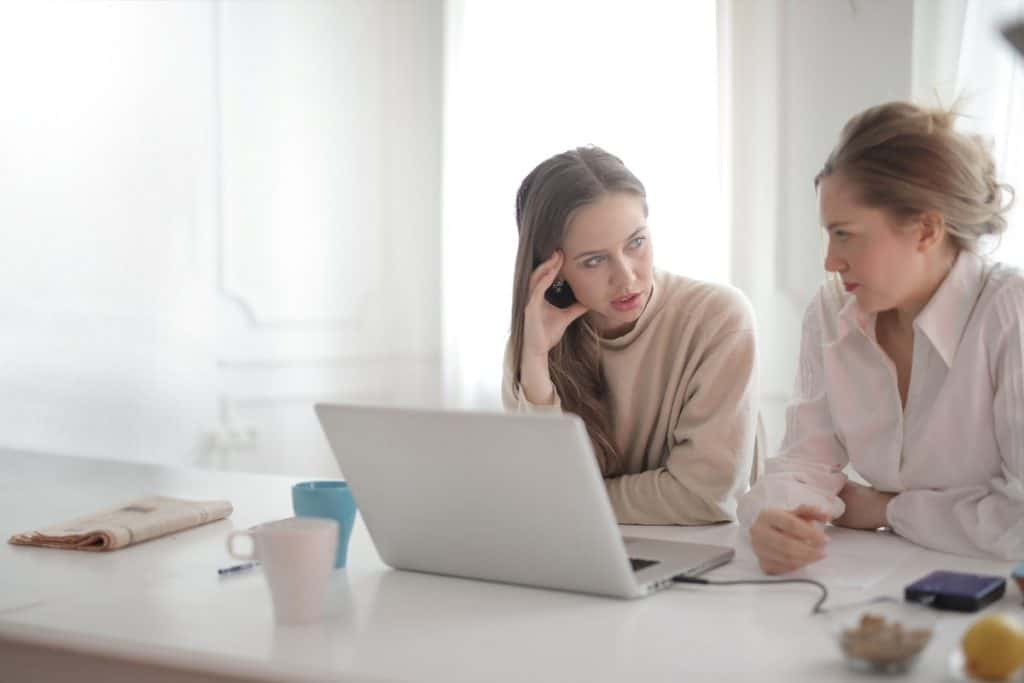 Two women behind a laptop discussing tech careers. Is Technology a Good Career Path?