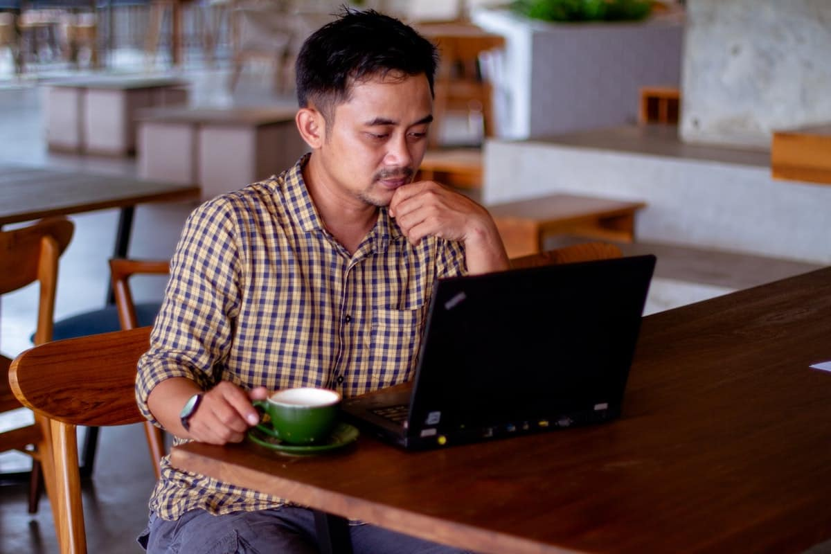 Computer programmer sitting at table with laptop and coffee What Jobs Can You Do as a Coder?
