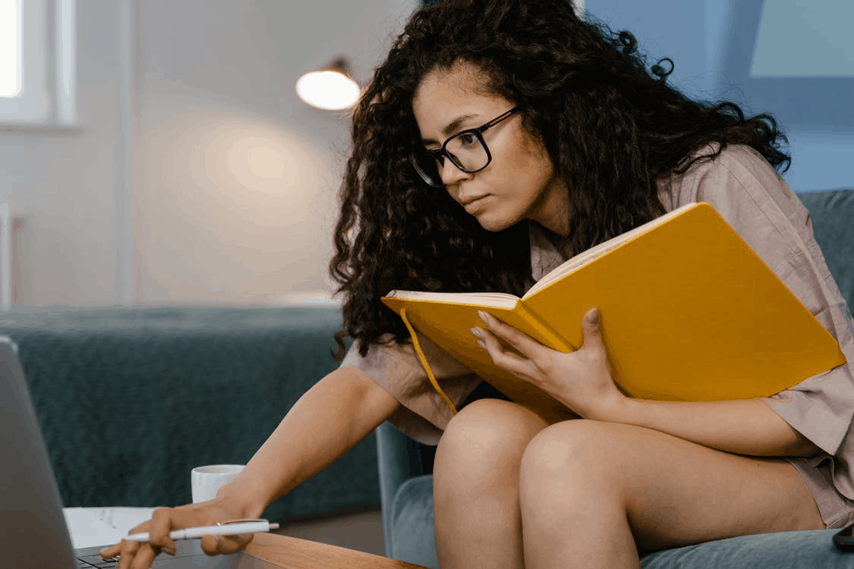 curly-haired woman studying object oriented programming techniques with a notebook and a laptop what is object oriented programming