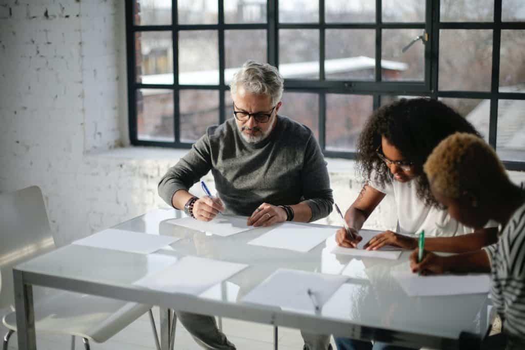 People writing on paper on a white desk Best Companies Offering Web Development Internships