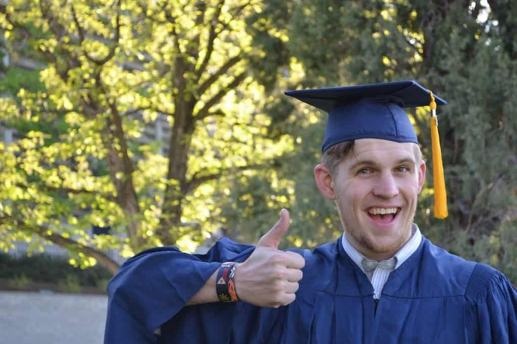 Young man giving a thumbs up after graduation Coding Bootcamp Cost