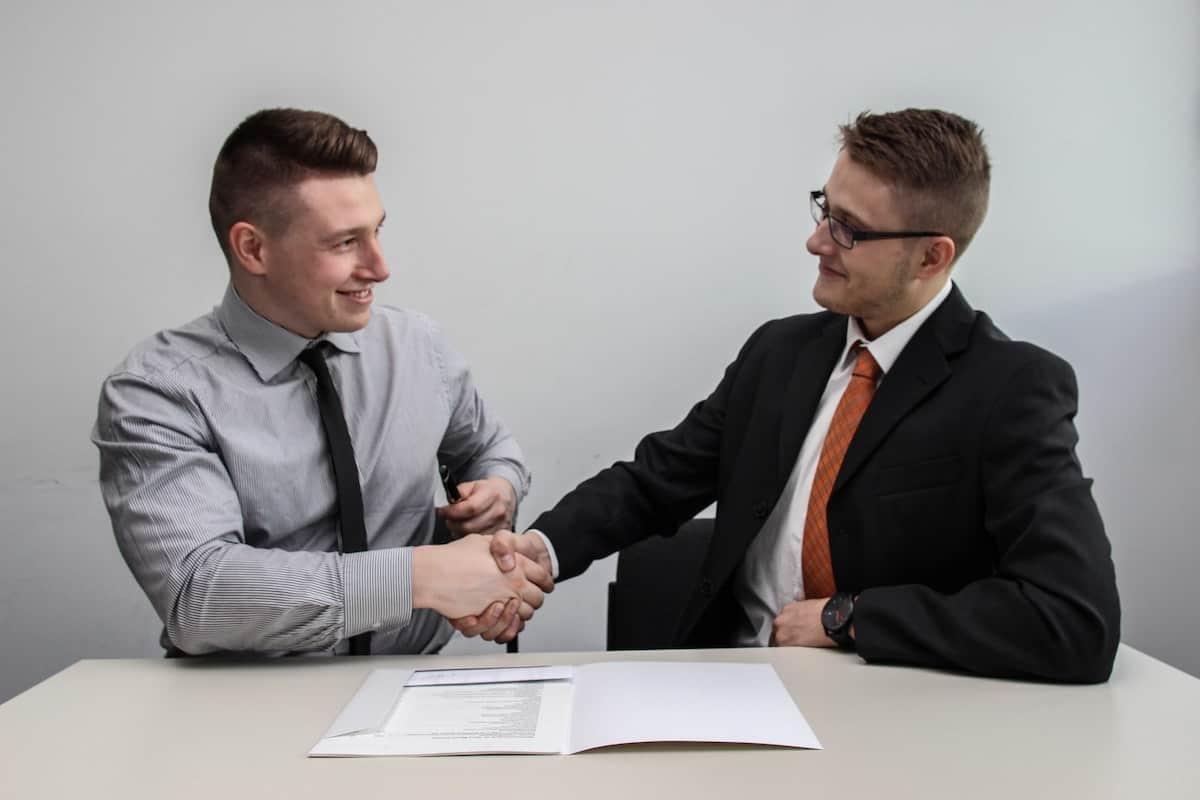 Two businessmen shaking hands. Top Software Development Interview Questions